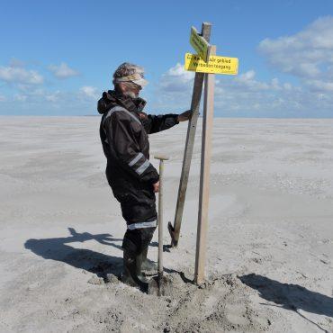 De Waddenunit plaatst een bord. FOTO: Bert Meerstra/Waddenunit